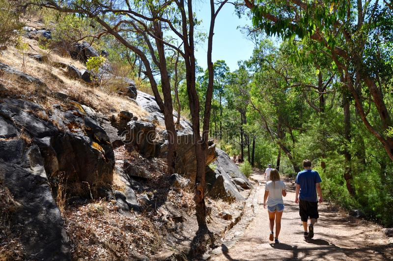 Hiking at Serpentine Falls. SERPENTINE,WA,AUSTRALIA-JANUARY 30,2014: Tourists hiking the trails with the natural granite rock face at Serpentine National Park royalty free stock images