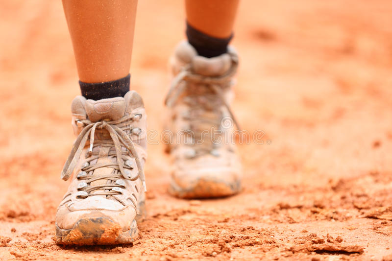 Hiking shoes - closeup of dirty hiker boots. Woman feet and female hikers shoe walking on dirt trail hike path outdoor in nature stock photos
