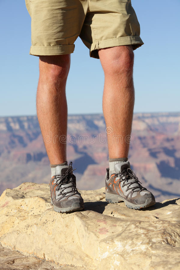 Hiking shoes on hiker in Grand Canyon. Man hikers hike boots in closeup with breathtaking view of Grand Canyon in the background. Male feet stock image