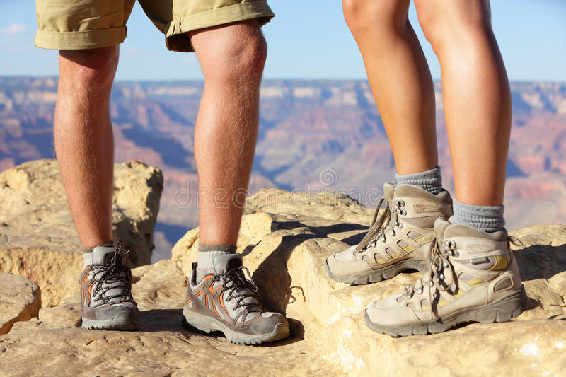 Hiking shoes on hikers in Grand Canyon. Man and women hiker hike boots in closeup with breathtaking view of Grand Canyon in the background. Male and female stock photo