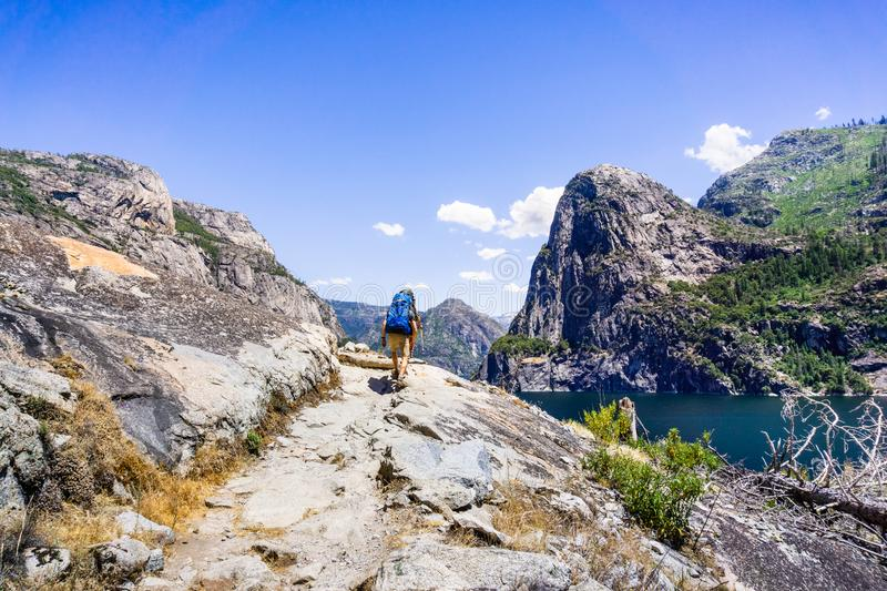 Hiking on the shoreline of Hetch Hetchy reservoir in Yosemite National Park, Sierra Nevada mountains, California; the reservoir is. One of the main sources of royalty free stock photography
