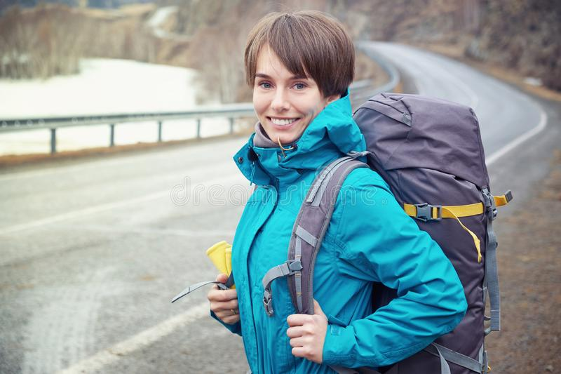 Hiking smiling woman with a backpack in mountains. Beautiful young girl is traveling in the mountains royalty free stock images