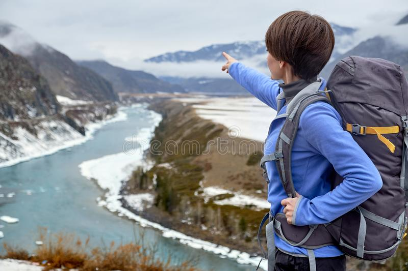 Hiking smiling woman with a backpack in mountains. Beautiful young girl is traveling in the mountains stock image