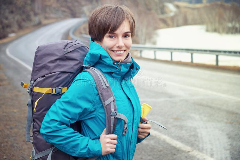 Hiking smiling woman with a backpack in mountains. Beautiful young girl is traveling in the mountains royalty free stock photo