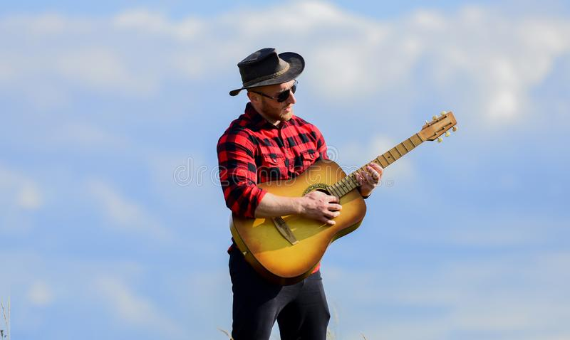 Hiking song. Handsome man with guitar. Country style. Summer vacation. Play beautiful melody. Country music concept. Guitarist country singer stand in field royalty free stock photos