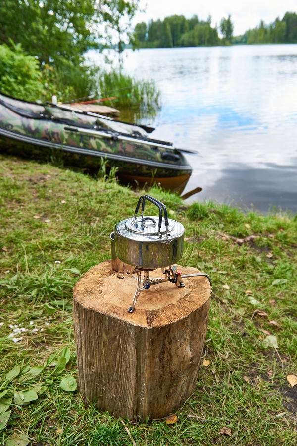 Hiking stove with kettle on stump and fishing boat stock photos