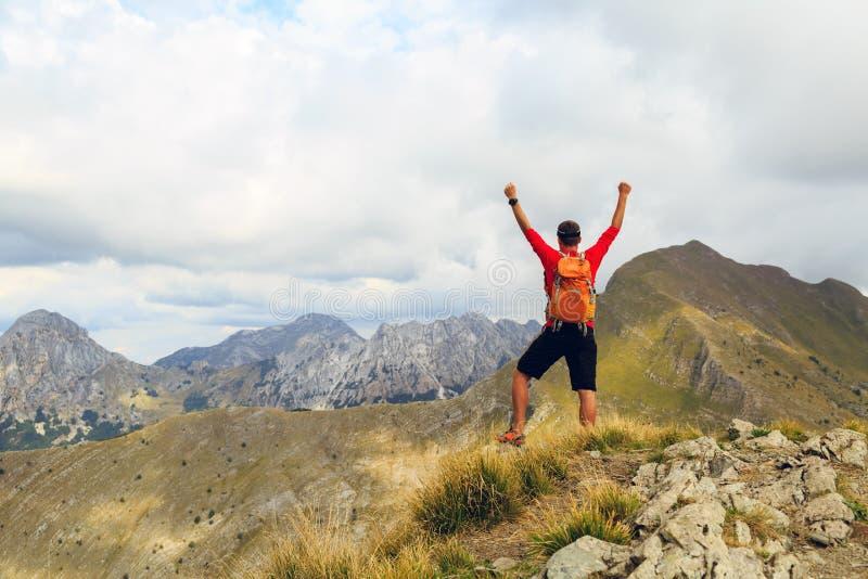 Hiking success, man runner in mountains stock photo