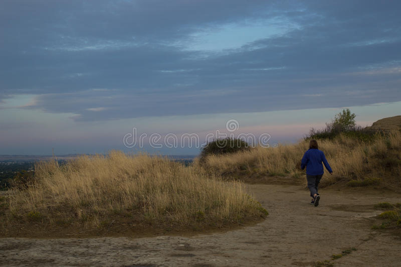 Hiking Swords Park Trail. Woman wearing a cornflower blue fleece jacket with her back to the camera walking along a dirt trail through dried vegetation toward a royalty free stock image