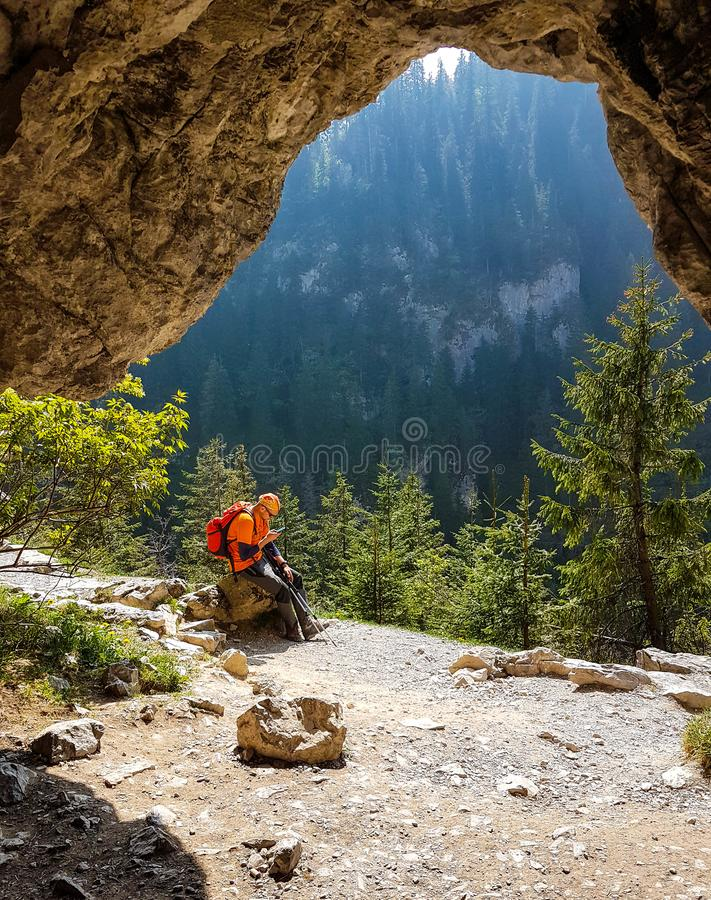 Hiking in Tatra National Park, Poland, in May. Beautiful panoramic view on rocky mountains. A hiker looking for route information royalty free stock photos