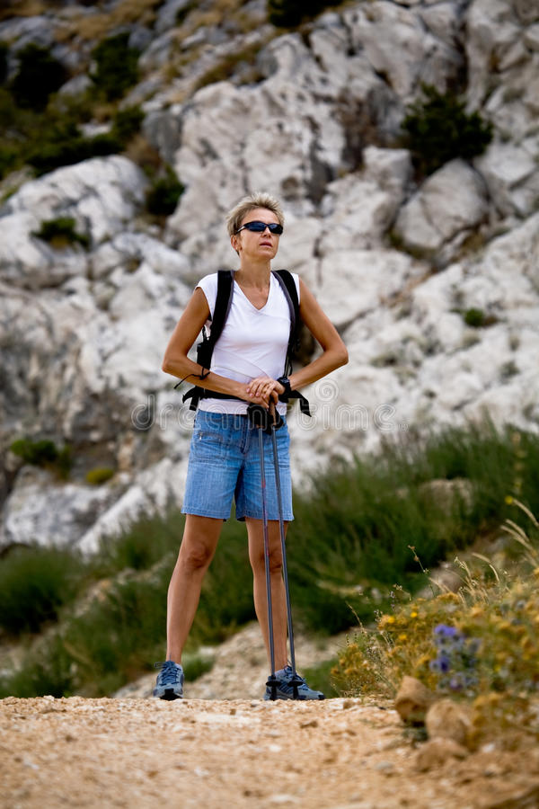 Hiking to the peak. Woman hiking in the mountains stock images