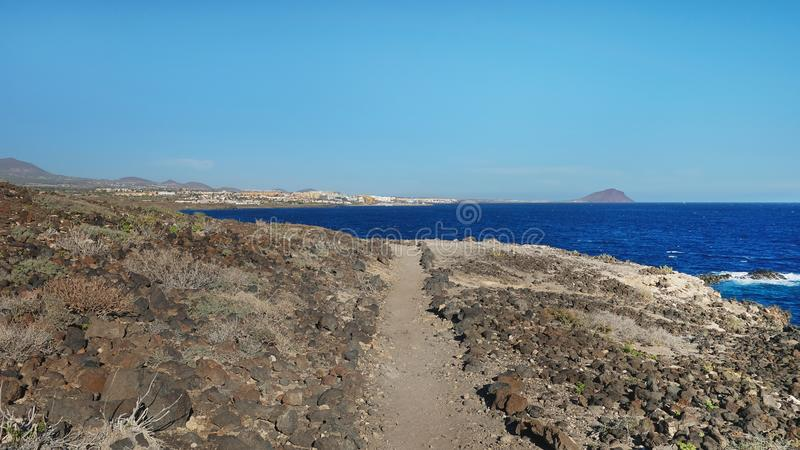 Hiking trail nearby Atlantic through the arid volcanic landscape of the island, Tenerife, Canary Islands, Spain royalty free stock photo