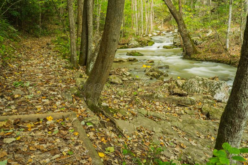 Hiking Trail by Roaring Run Creek. An autumn view of a hiking trail by Roaring Run Creek at Roaring Run Recreational Area located the mountains of the Jefferson royalty free stock image