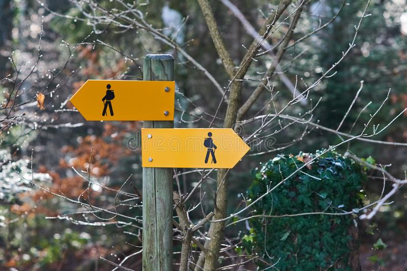 Hiking trail signs with hiker figures stock images