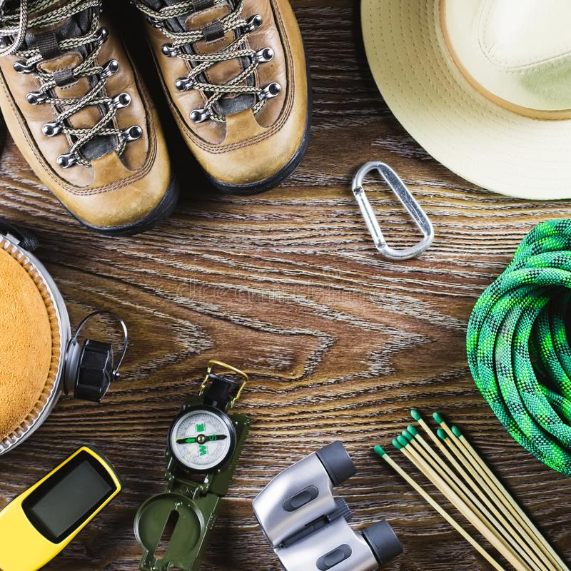 Hiking equipment with boots, compass, binoculars, matches, travel bag on wooden background. Active lifestyle concept. Hiking or travel equipment with boots royalty free stock images