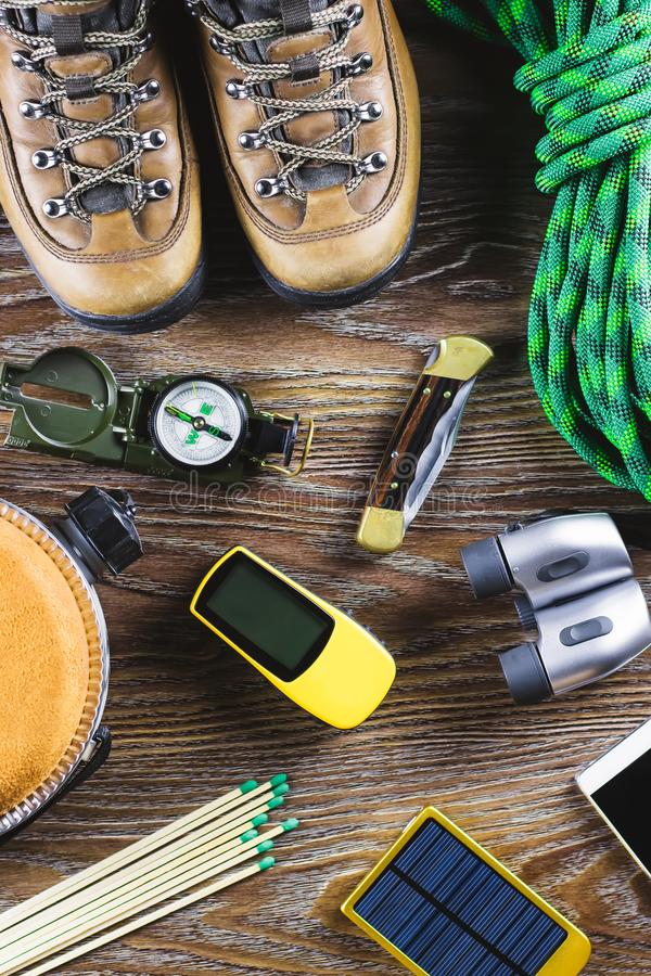 Hiking or travel equipment with boots, compass, binoculars, matches on wooden background. Active lifestyle concept stock photography