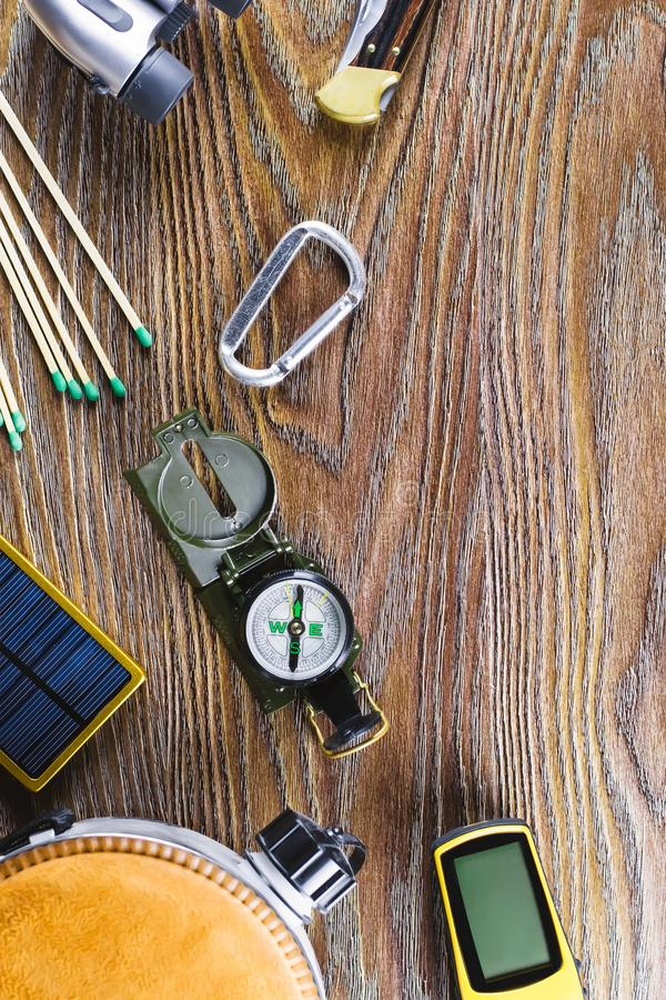 Hiking or travel equipment with boots, compass, binoculars, matches on wooden background. Active lifestyle concept royalty free stock image