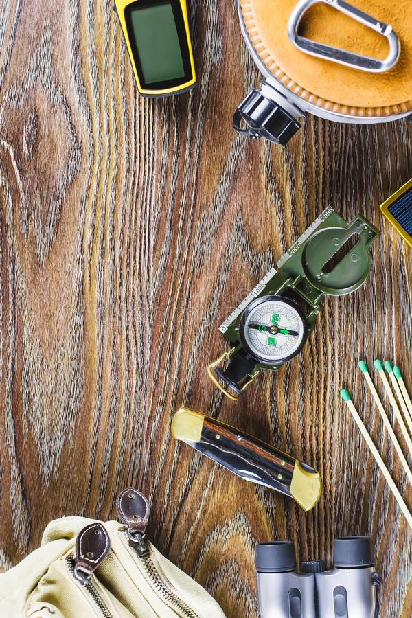Hiking or travel equipment with boots, compass, binoculars, matches on wooden background. Active lifestyle concept stock photo