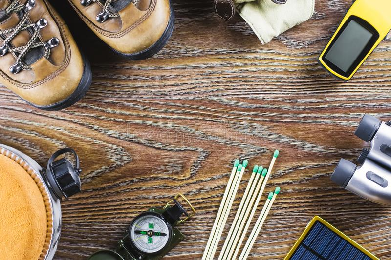 Hiking or travel equipment with boots, compass, binoculars, matches on wooden background. Active lifestyle concept stock image