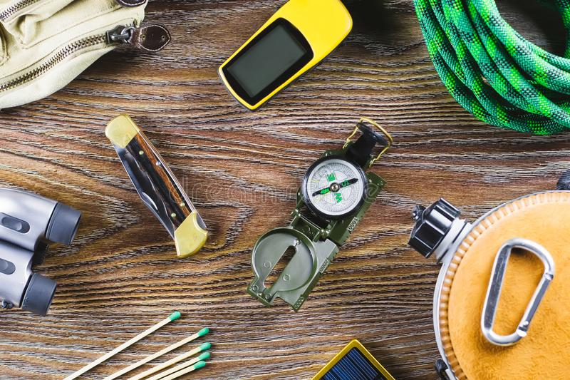 Hiking or travel equipment with boots, compass, binoculars, matches on wooden background. Active lifestyle concept. Top view royalty free stock photo