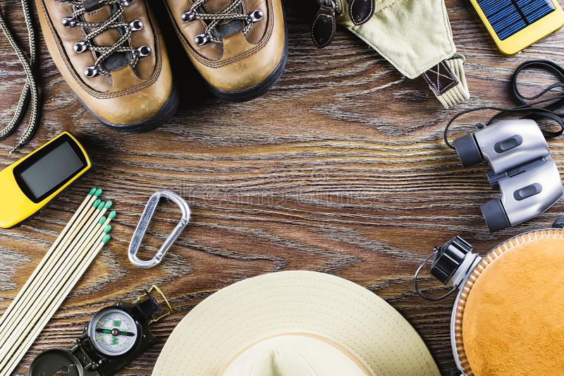 Hiking or travel equipment with boots, compass, binoculars, matches on wooden background. Active lifestyle concept. stock photo