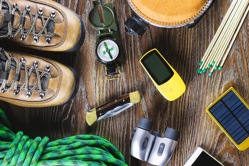 Hiking or travel equipment with boots, compass, binoculars, matches on wooden background. Active lifestyle concept. Top view royalty free stock photography