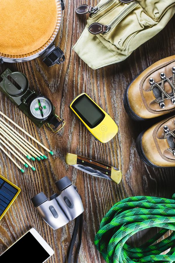 Hiking or travel equipment with boots, compass, binoculars, matches on wooden background. Active lifestyle concept. Top view stock photos