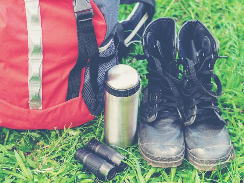 Hiking travel gear on glasses. Items include hiking boots, cup, map, binoculars. Flat lay of outdoor travel equipment items for mountain camping trip royalty free stock photos