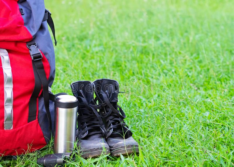 Hiking travel gear on glasses. Items include hiking boots, cup, map, binoculars. Flat lay of outdoor travel equipment items for mountain camping trip stock photo