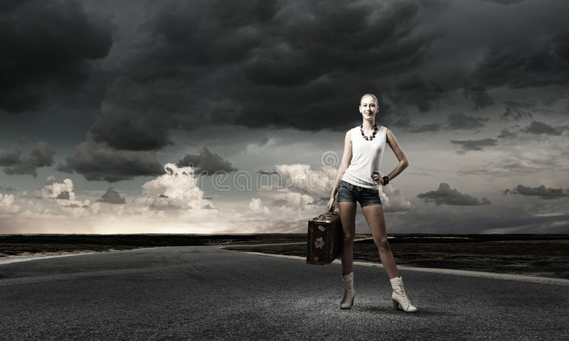 Hiking traveling. Young woman hiker standing with suitcase in hand royalty free stock photography