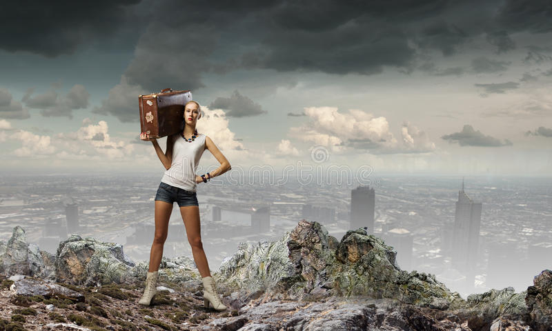 Hiking traveling. Young woman hiker walking with suitcase on shoulder stock image