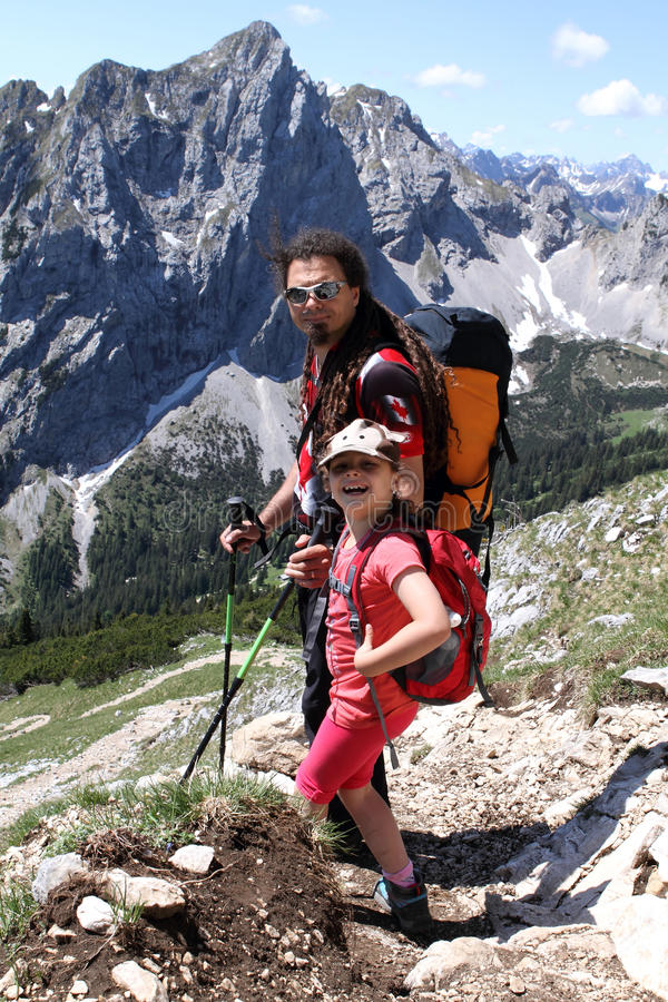 Hiking trekking child and father in the Alps stock images
