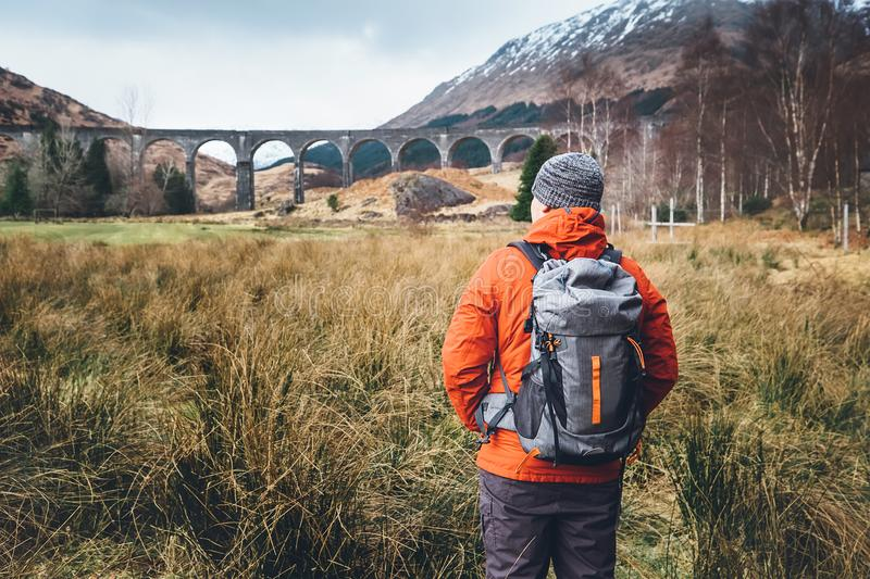 Hiking, walk with backpack, active lifestyle concept image. Man traveler walks neaar famous Glenfinnan viadukt in Scotland royalty free stock photos