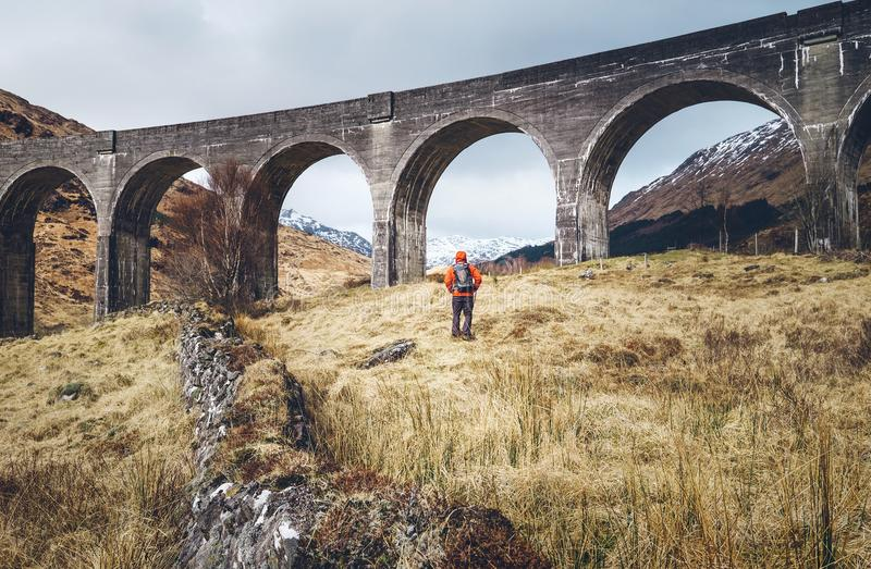Hiking, walk with backpack, active lifestyle concept image. Man. Traveler walks neaar famous Glenfinnan viadukt in Scotland royalty free stock photos