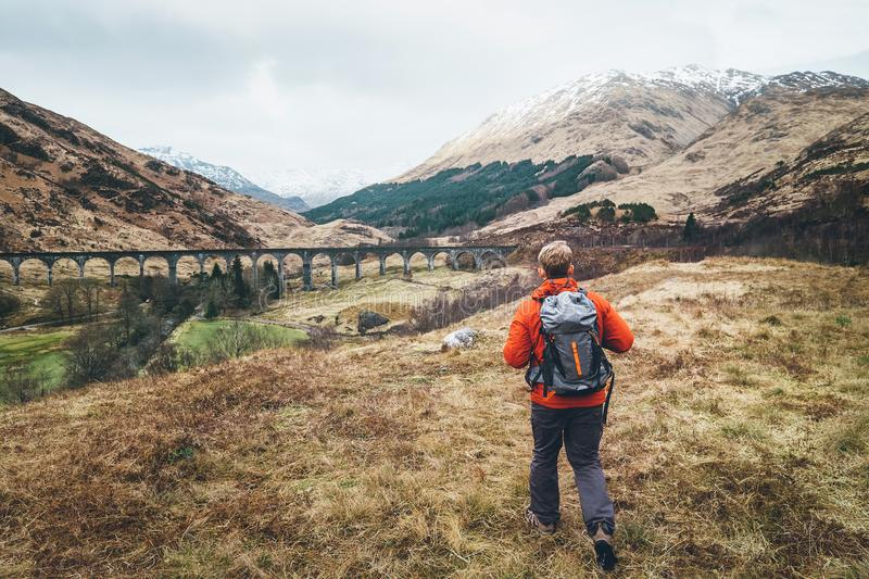 Hiking, walk with backpack, active lifestyle concept image. Man. Traveler walks neaar famous Glenfinnan viadukt in Scotland stock image