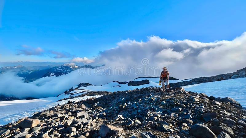 Hiking in Washington State. Man hiker walking up mountains above clouds. Rocky mountains under snow. Mount Rainier National Park. Seattle. WA. United States of royalty free stock photo