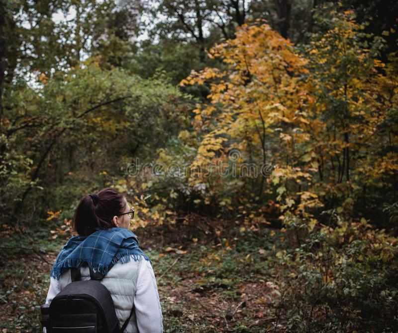 Hiking woman at autumn forest. Backpacker standing in woodland during fall season. Enjoying hike in nature at sunny day royalty free stock photos