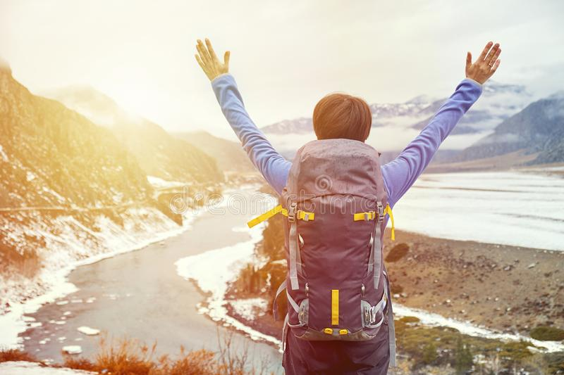 Hiking woman with a backpack at sunset raised her hands. Beautiful young girl is traveling in the mountains stock photography