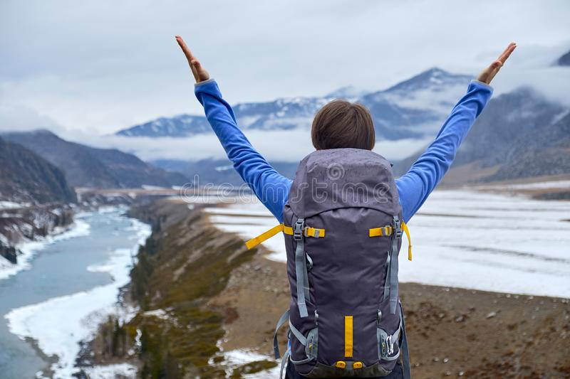 Hiking woman with a backpack at sunset raised her hands. Beautiful young girl is traveling in the mountains stock photo