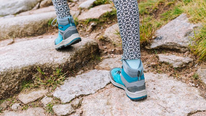 Hiking woman with boots on stone trail - walking in mountains royalty free stock photography