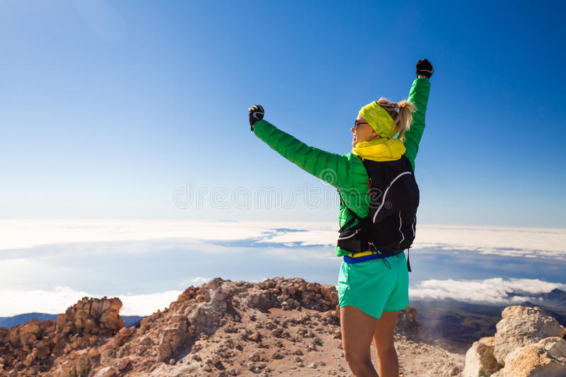 Hiking woman climbing in mountains on Teide Tenerife. Successful hiking climbing woman with backpack on Teide mountain top, Tenerife. Looking at inspirational stock photo