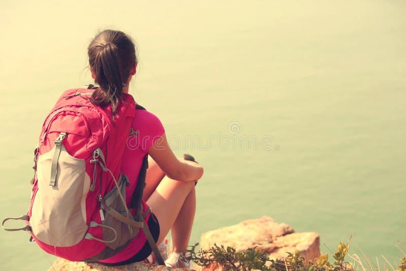 Hiking woman sit seaside rock royalty free stock photography