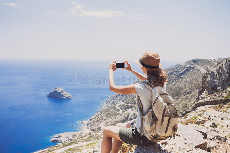 Hiking woman using smart phone taking photo, travel and active lifestyle conceptt stock image