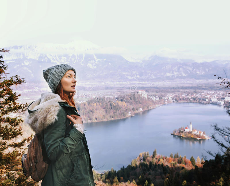 Hiking young woman with alps mountains and alpine lake on background. Travel Slovenia, Europe. Top view on Island with Catholic Church in Bled Lake with Castle royalty free stock image