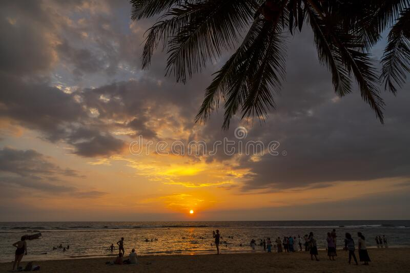 Sunset on the ocean. Tourists are photographed on the shore. Hikkaduwa, Sri Lanka. March 1, 2018.  Sunset on the ocean. Tourists are photographed on the shore royalty free stock image