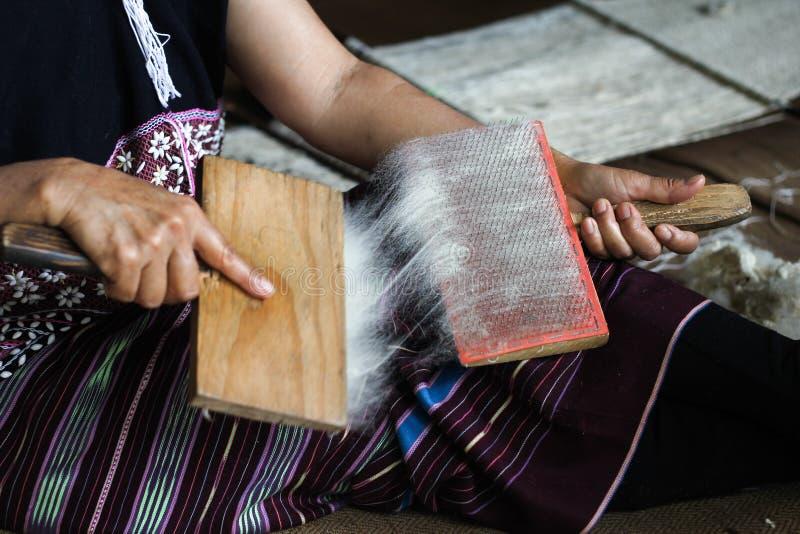 Hilado de lanas de cepillado de la mujer de Karen con el cepillo especial fotos de archivo libres de regalías