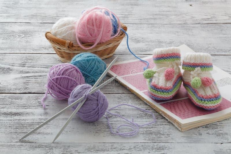 Hilado de lanas en bobinas con las agujas que hacen punto en cesta de mimbre en lig foto de archivo