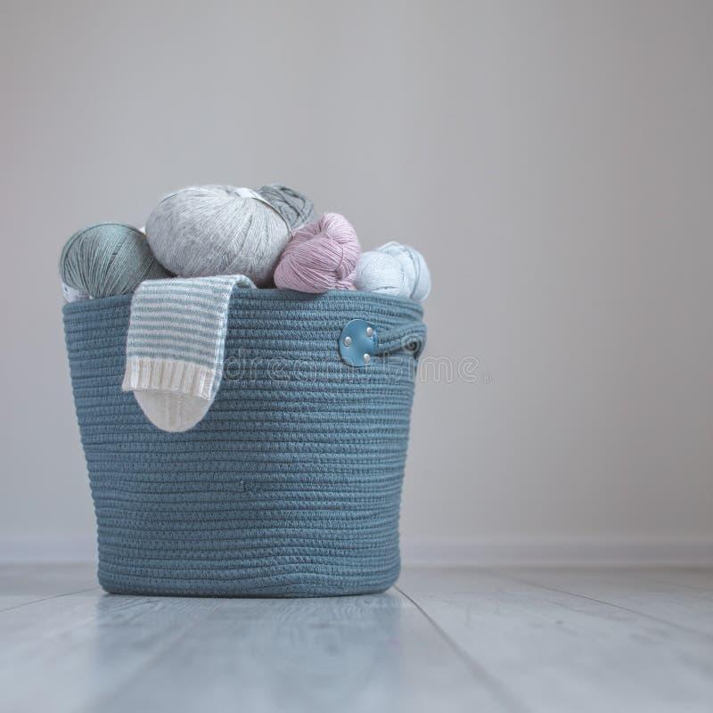 Hilado de lanas en bobinas con los calcetines rayados adentro a la cesta tejida hecha a mano del hilo del algodón imágenes de archivo libres de regalías