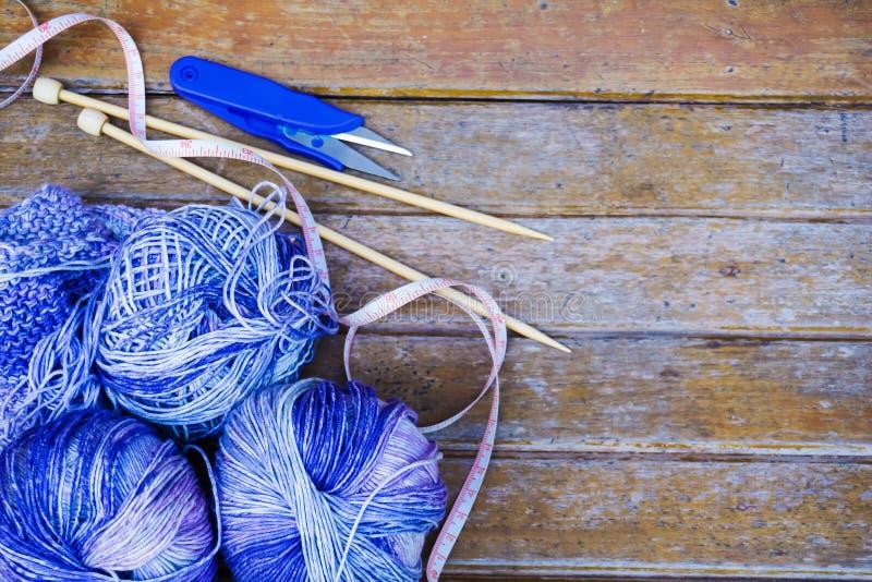 Hilado púrpura que hace punto en fondo de madera/hacer punto natural de las lanas fotos de archivo