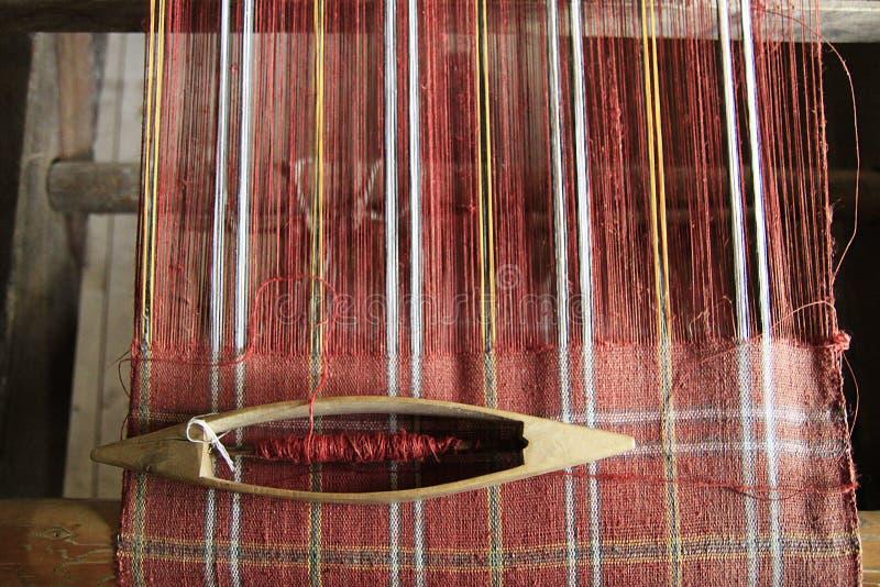 Hilado rojo en el telar con la lanzadera que teje imágenes de archivo libres de regalías