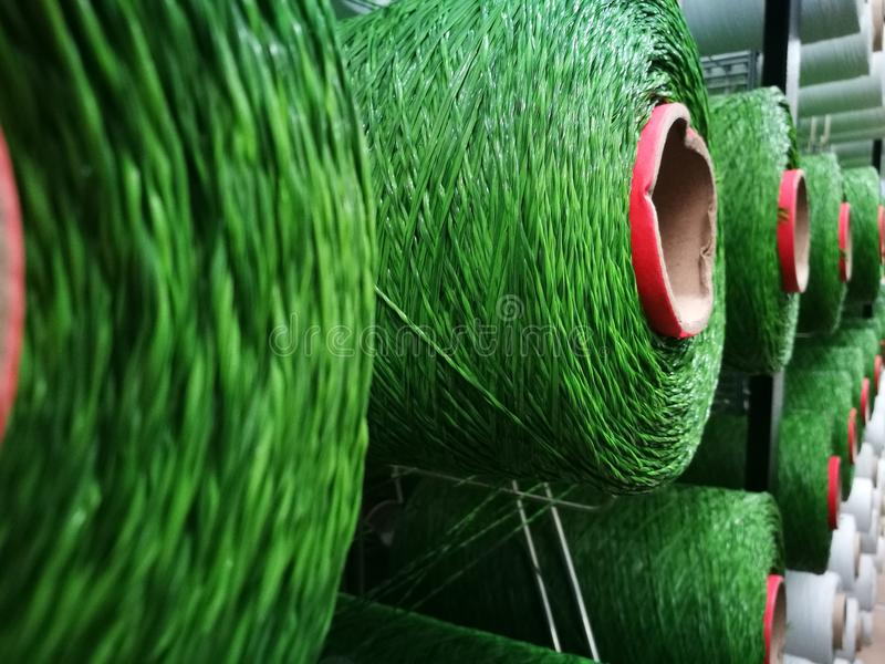 Hilados blancos y verdes en los estantes para los telares de la hierba artificial fotografía de archivo libre de regalías